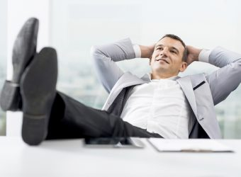 Smiling businessman resting his legs on the desk and enjoying himself.   [url=http://www.istockphoto.com/search/lightbox/9786622][img]http://dl.dropbox.com/u/40117171/business.jpg[/img][/url]