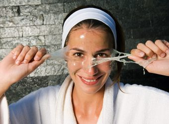 Woman peeling face mask --- Image by © Image Source/Corbis